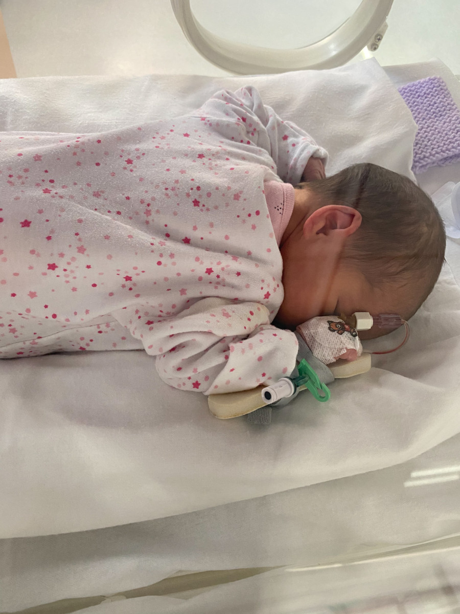 Aurora in the NICU wearing a sleep suit with a cannula fitted in her hand