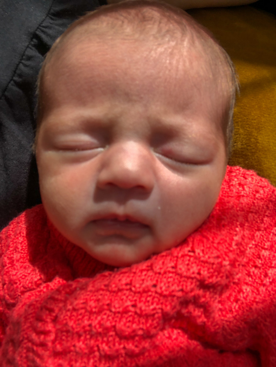 Aurora sleeping in a coral coloured knitted cardigan