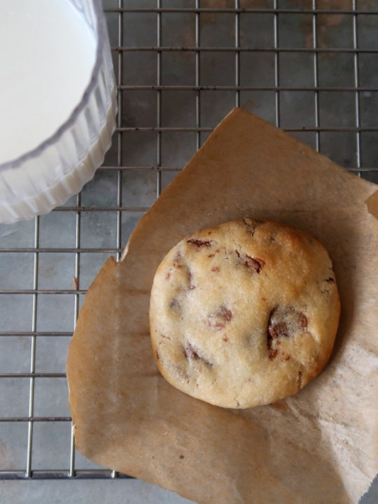 An air fryer cookie on parchment paper on a cooling rack with a glass of milk