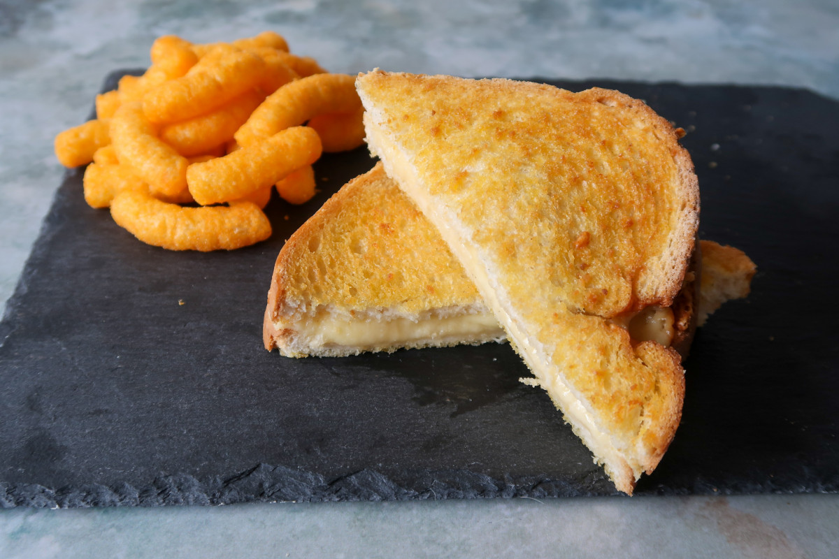Air fryer grilled cheese on a slate with flaming hot Wotsits in the background