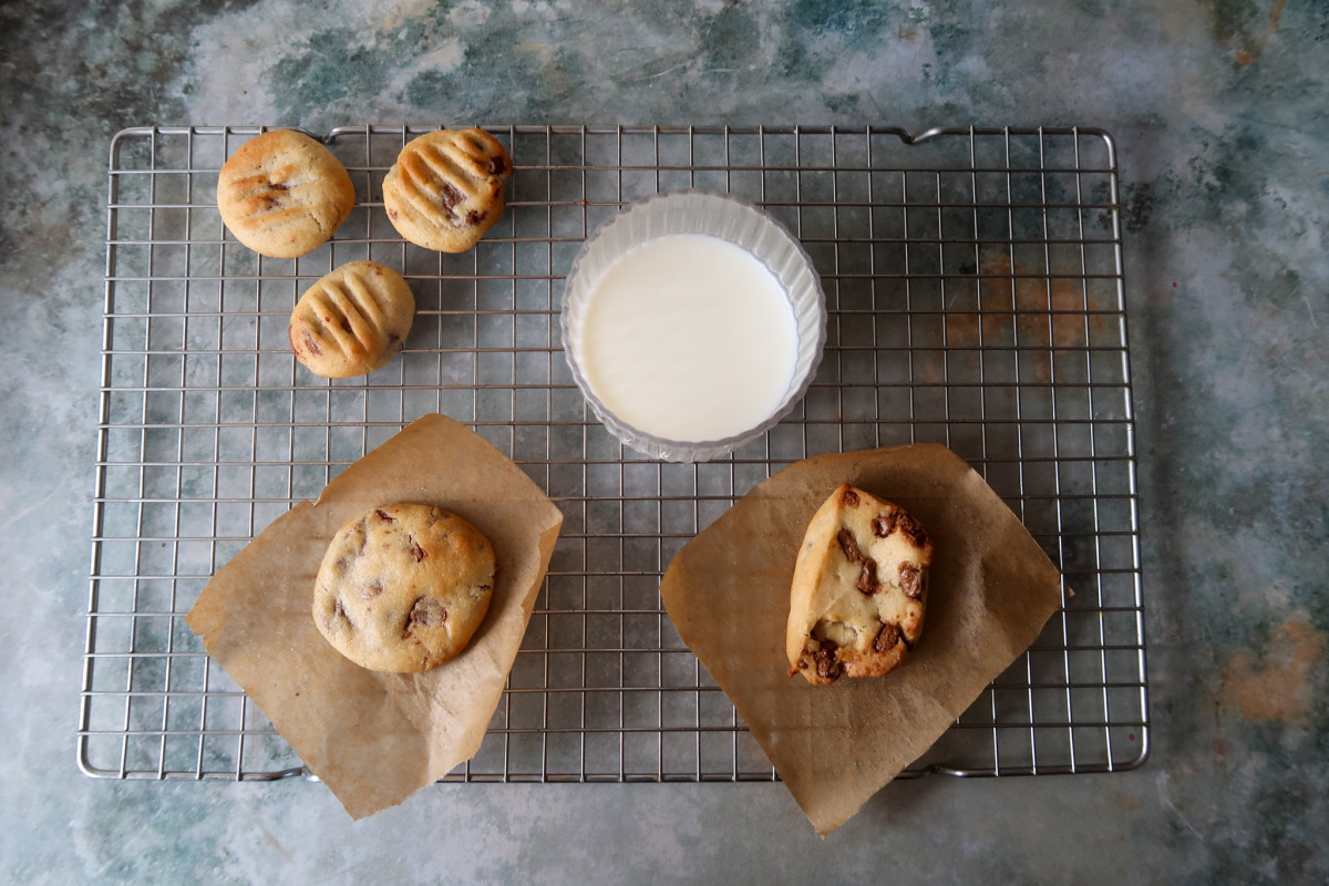 Mini air fryer cookies, a large air fried cookie and cookie dough cooked in the air fryer on a cooling rack with a glass of milk