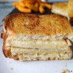 A cooked air fryer grilled cheese sandwich cut in half on a plate