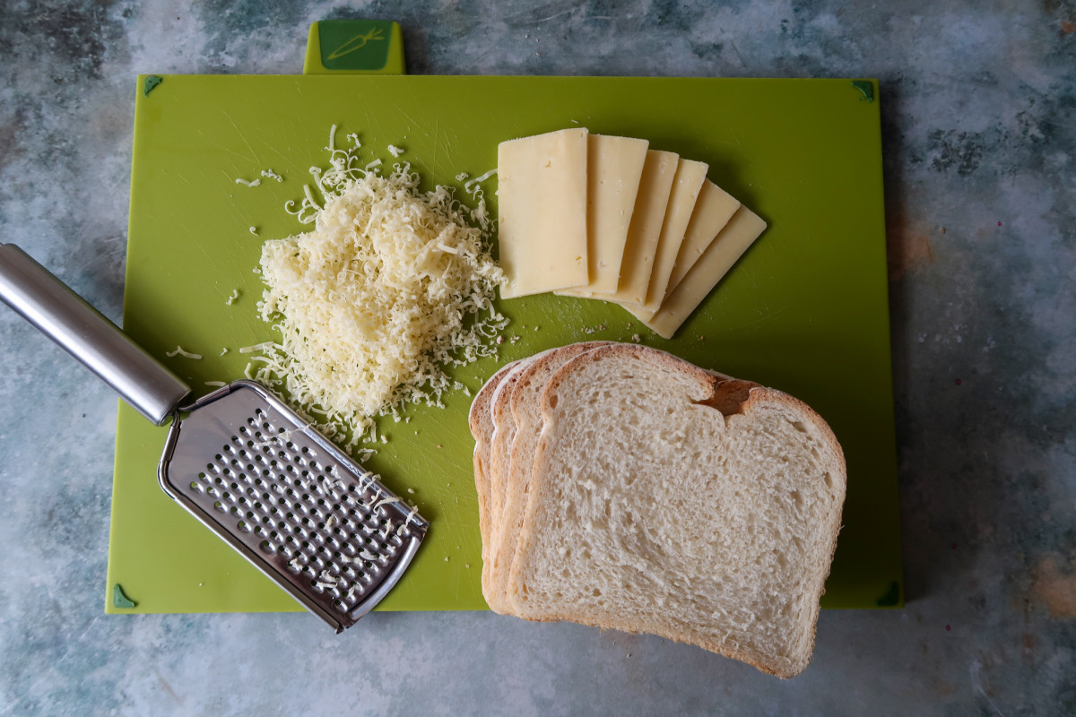 A green chopping board with sliced and grated cheddar cheese, crusty bread and a microplane grater