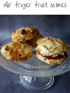 air fryer fruit scones on a glass cake stand decorated with jam and cream
