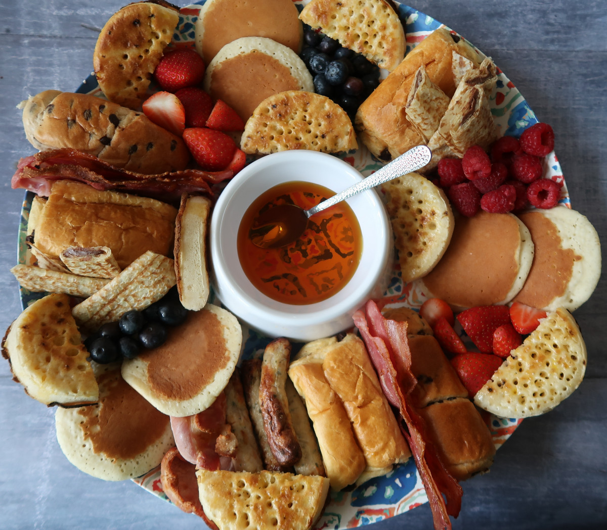 A breakfast platter containing crumpets, bacon, sausages, pain au chocolat, brioche rolls, fruit, and pancakes