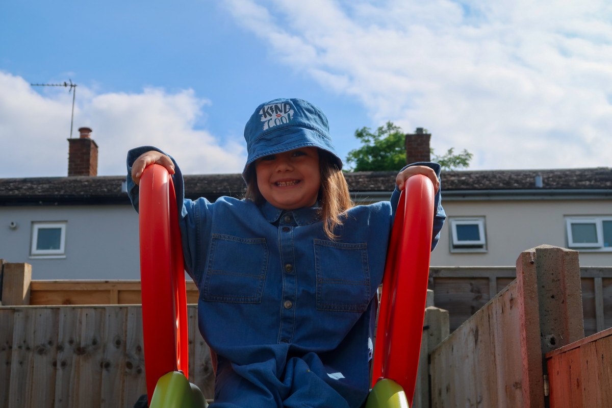 Daisy sitting on the Smoby Megagliss slide in our back garden