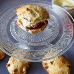 A jam and cream dressed air fryer fruit scone on a glass cake stand with air fryer fruit scones around it and jam and cream in serving dishes.