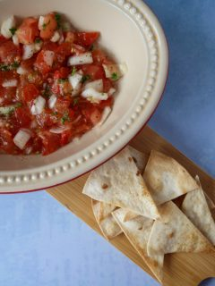 Chunky tomato salsa in a serving dish with a serving board of air fryer tortilla chips