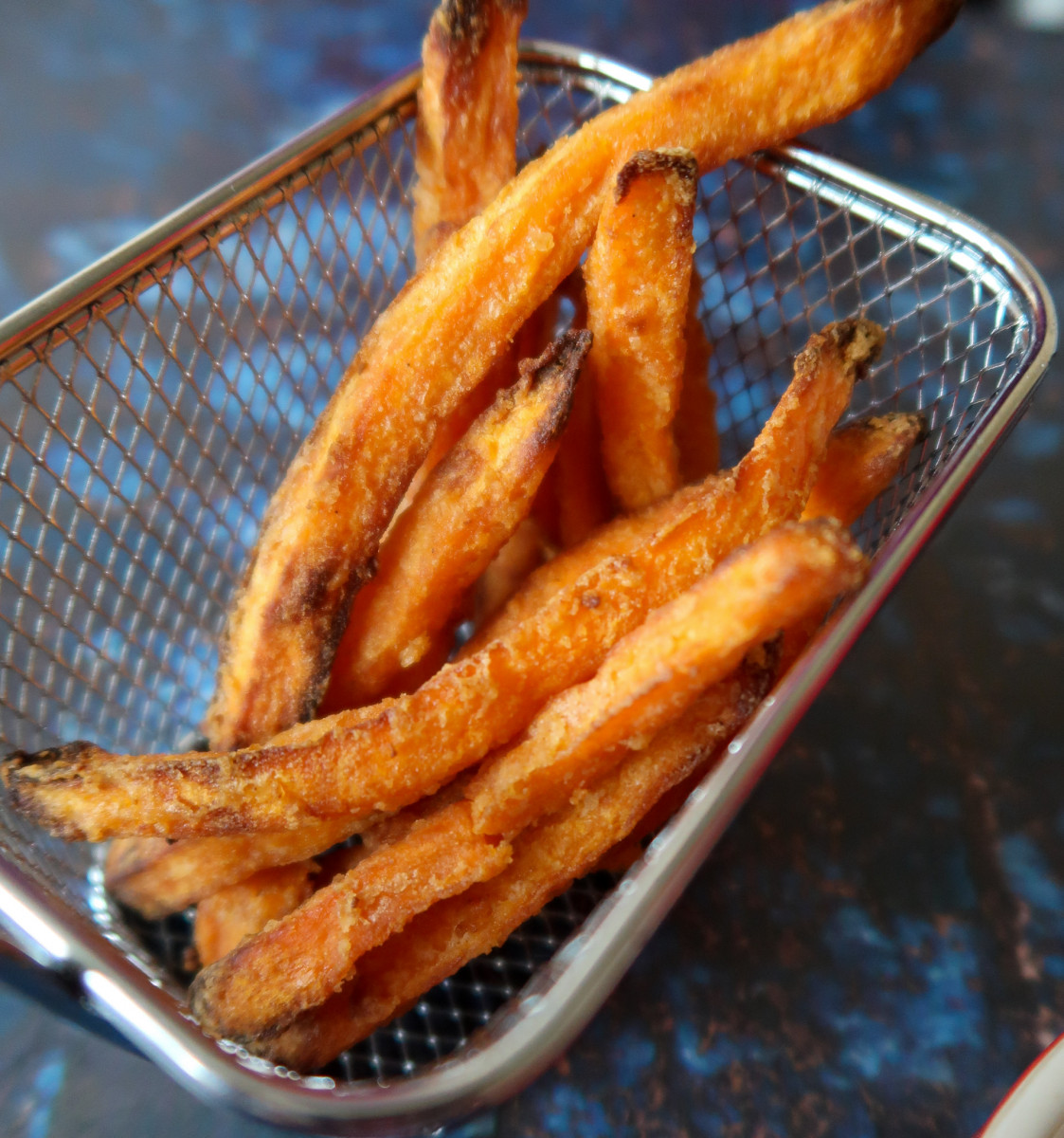 Frozen sweet potato fries cooked in the air fryer served in a metal basket with a Le Creuset ramekin of tomato ketchup