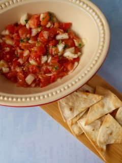 Tomato and chilli salsa in a serving dish with a side of air fryer tortilla chips on a wooden board