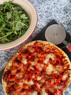 A cooked pizza, made in the air fryer, on a slate board with a pizza cutter and a rocket salad dressed with balsamic vinegar