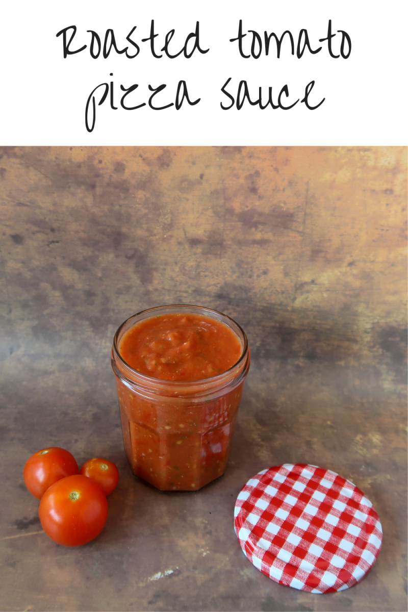 roasted tomato pizza sauce in a glass jar with red tomatoes to the side and a patterned lid